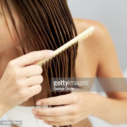 close-up of a woman combing her wet hair : Stock-Foto