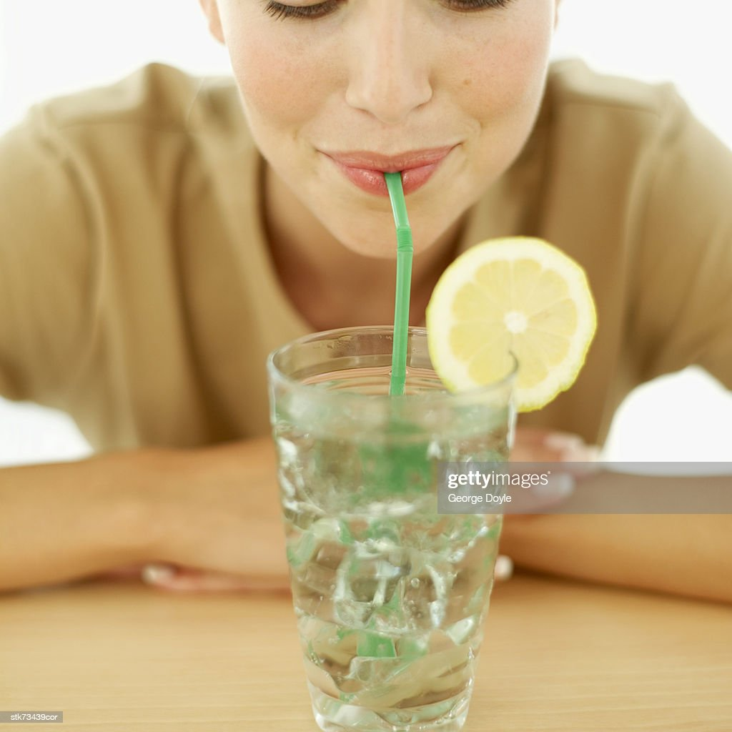 close-up of a woman drinking lemonade with a straw : Stock Photo