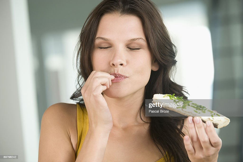 Close-up of a woman eating a bread : Stock Photo