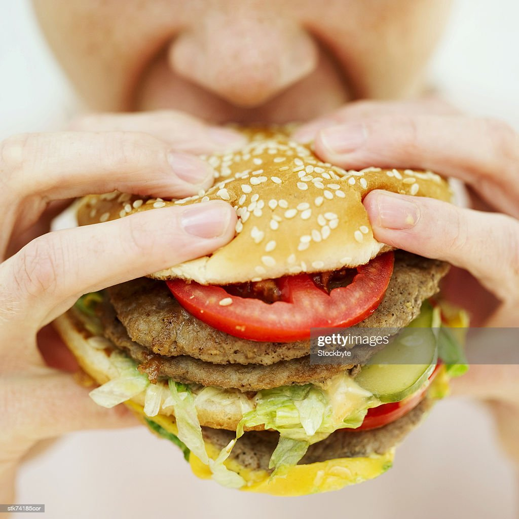 Close-up of a woman eating a hamburger : Stock Photo