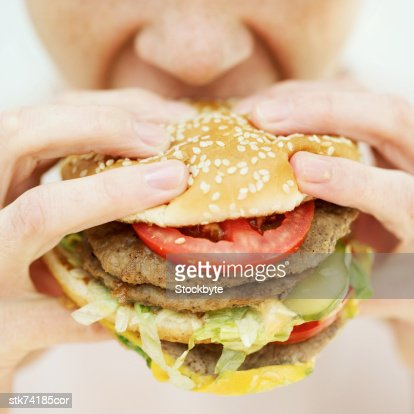 Close-up of a woman eating a hamburger : ストックフォト