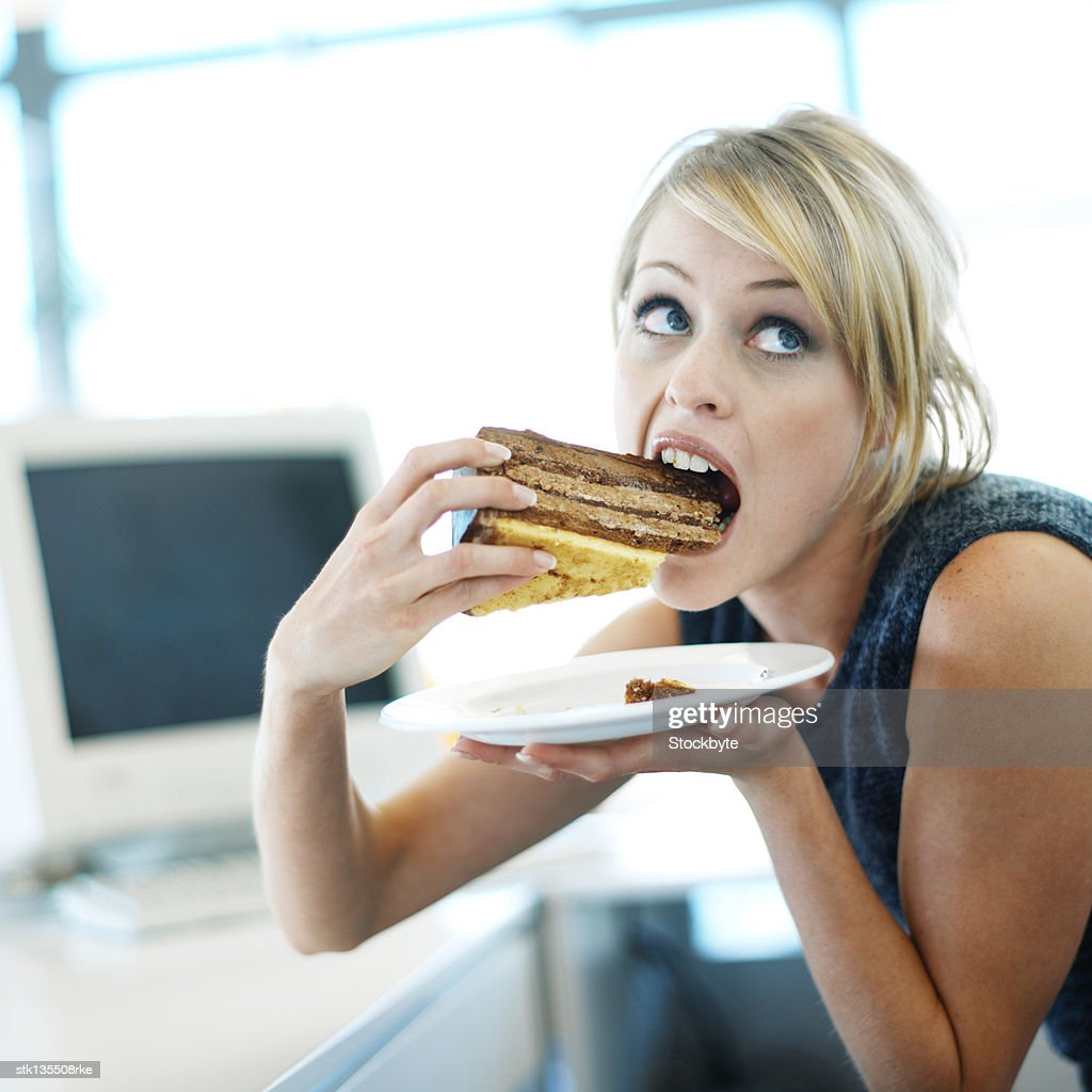 close-up of a woman eating a large piece of cake : Stock Photo