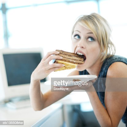 close-up of a woman eating a large piece of cake : Photo