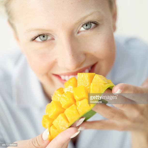 close-up of a woman eating a segmented slice of a mango
