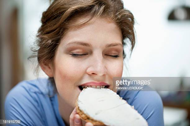 Close-up of a woman eating toast with cream spread on it