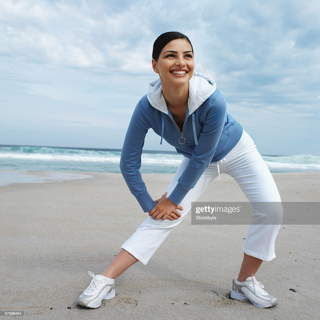 Close-up of a woman exercising on the beach : Stock Photo