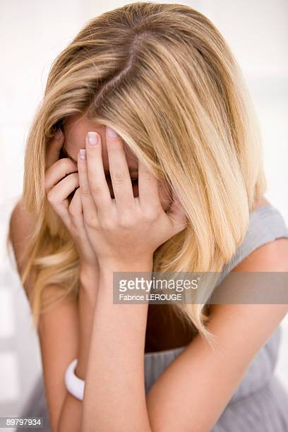 Close-up of a woman hiding her face with her hands