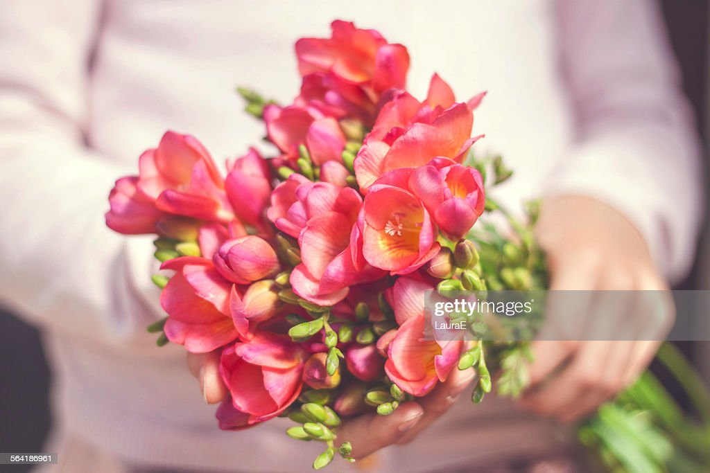 Close-up of a woman holding a bunch of freesia flowers
