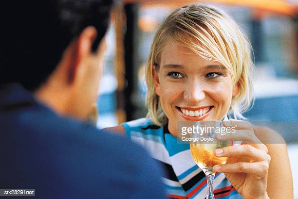 close-up of a woman holding a glass of wine and smiling at a man