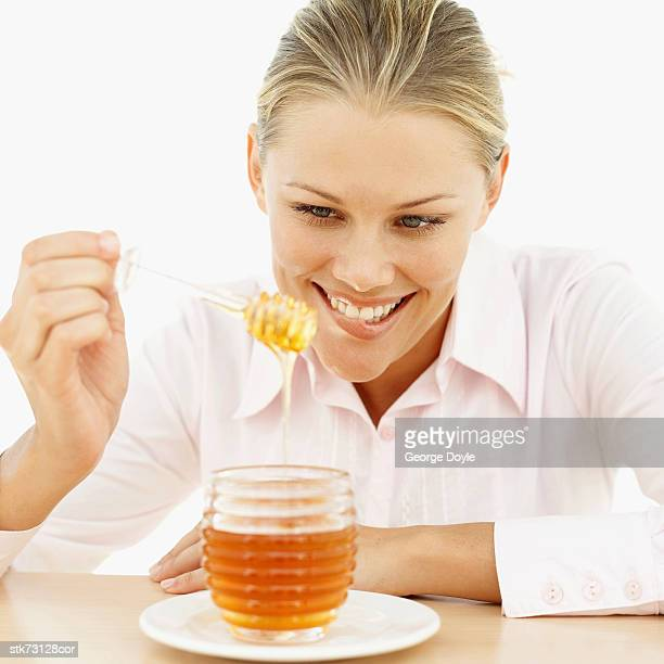 Close-up of a woman holding a honey dipper in a pot of honey