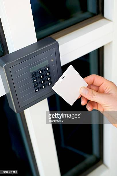 Close-up of a woman holding a magnetic card up to the security keypad and reader at the entrance to a secured building