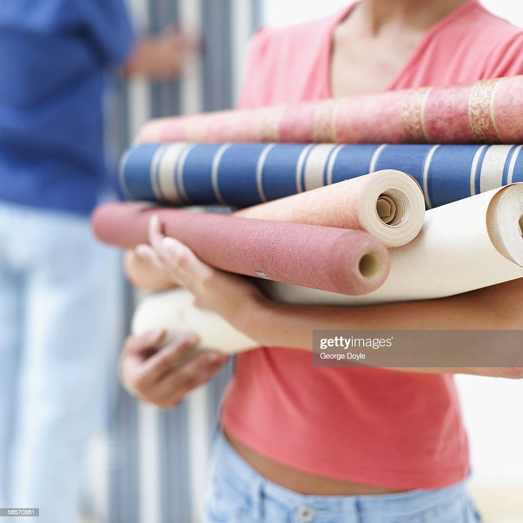 close-up of a woman holding rolls of assorted wallpaper : Stock Photo