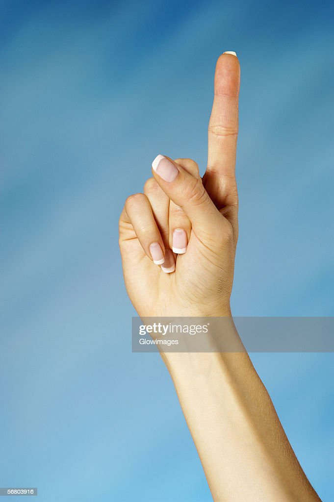 Closeup Of A Woman Holding Up One Finger Stock Photo