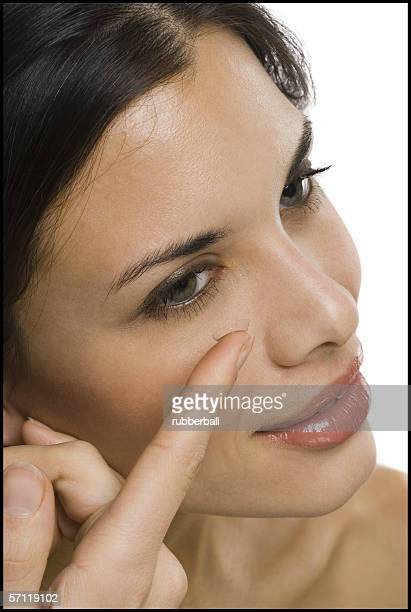 Close-up of a woman inserting a contact lens in her eyes