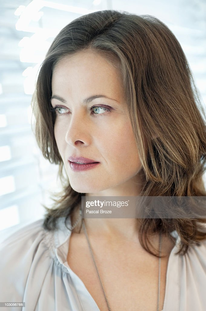 Close-up of a woman looking out of a window