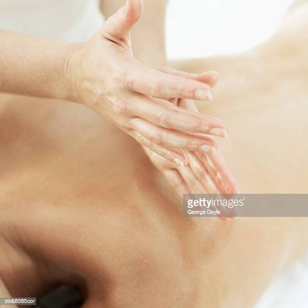 close-up of a woman massaging a man's back