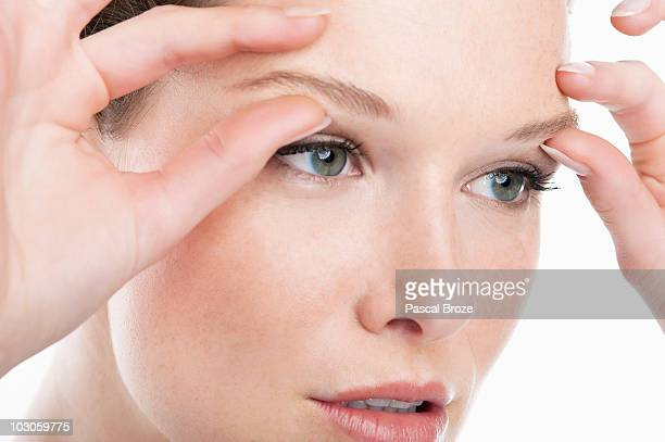 Close-up of a woman massaging eyebrows