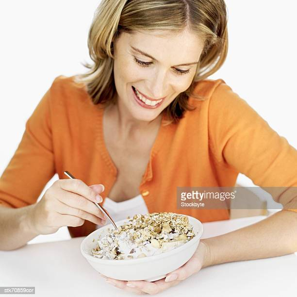 Close-up of a woman mixing yogurt with bowl of cereal