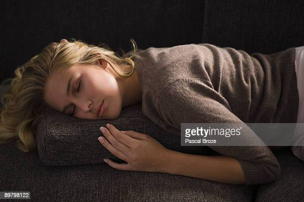 Close-up of a woman napping on a couch