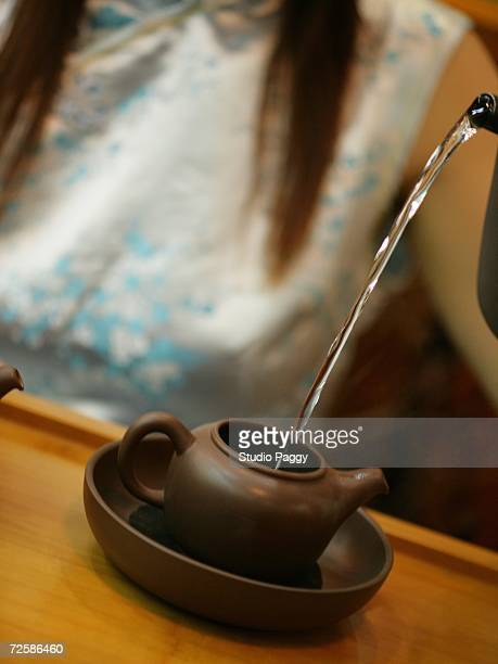 Close-up of a woman pouring water in a teapot