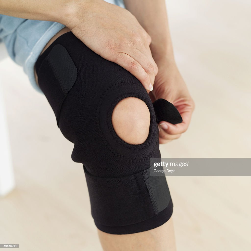 close-up of a woman putting on a knee pad