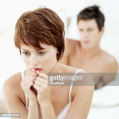 close-up of a woman sitting in a pensive mood with a man behind her : Stockfoto