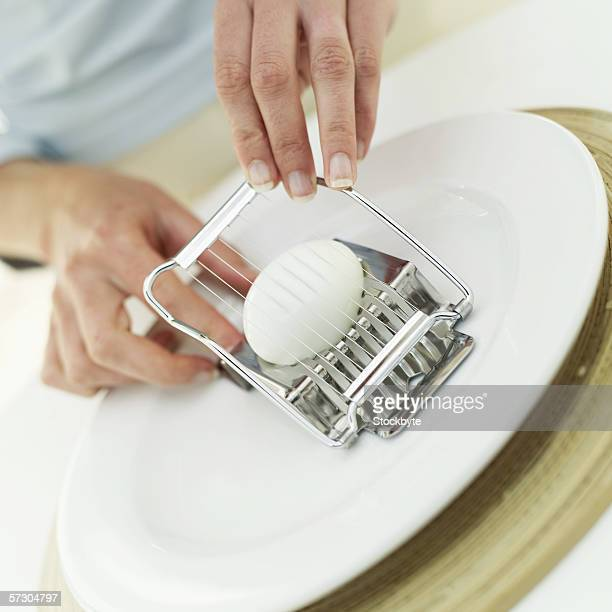 Close-up of a woman slicing a hard boiled egg using a slicer