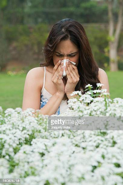 Close-up of a woman sneezing near flowers