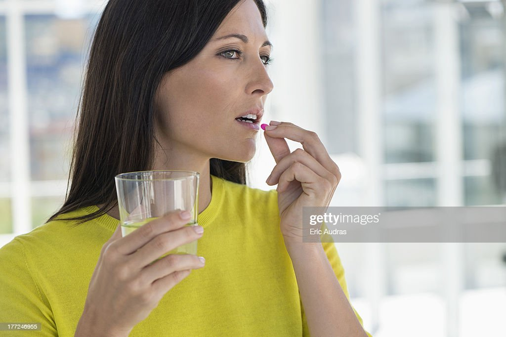 Close-up of a woman taking medicine