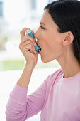 Close-up of a woman using an asthma inhaler