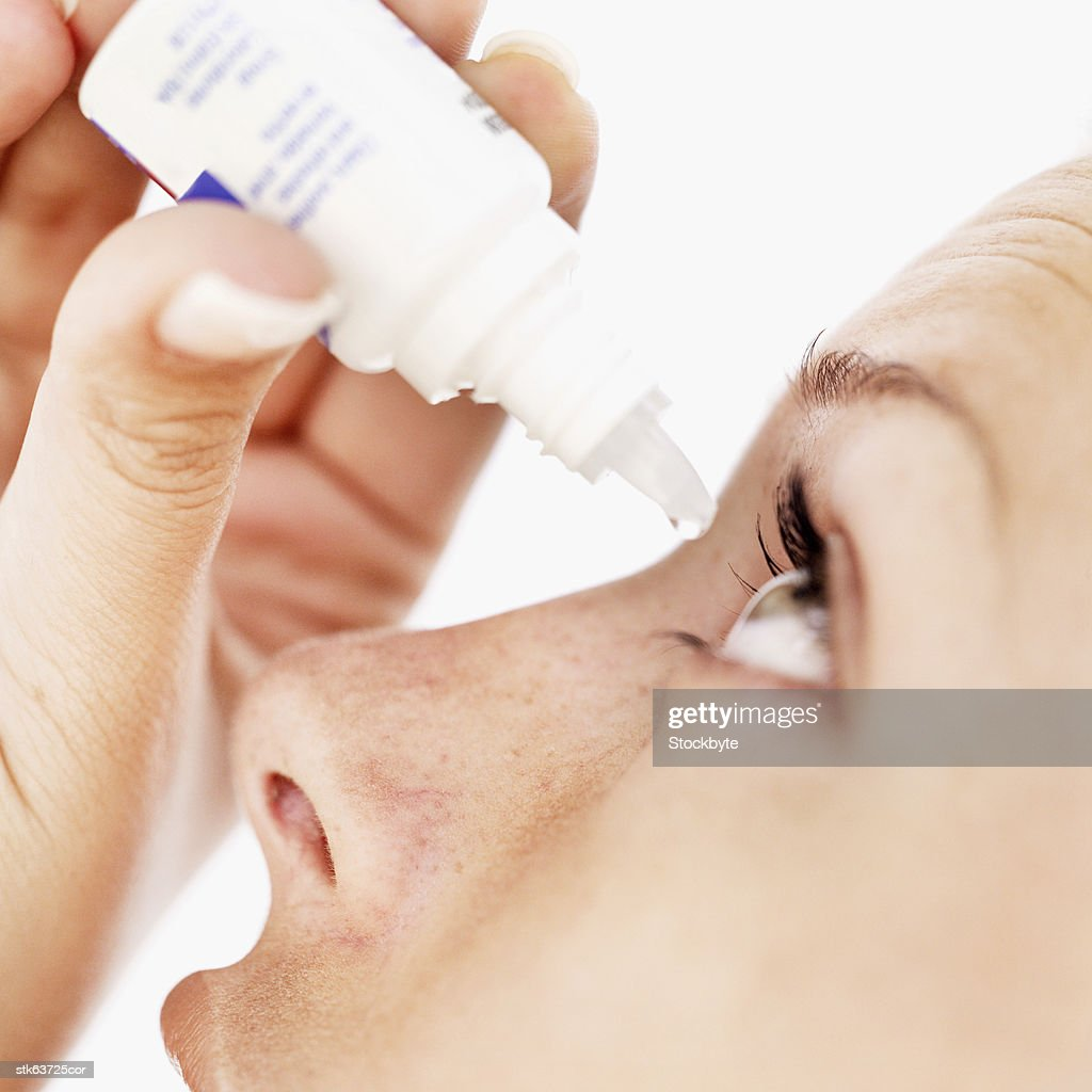 close-up of a woman using eye drops