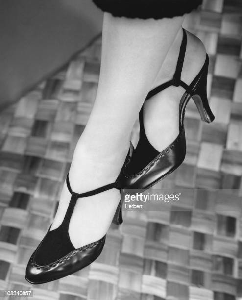 A closeup of a woman wearing a pair of highheeled Tstrap shoes circa 1950