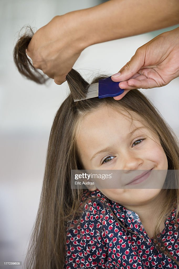 Close-up of a woman's hand combing her daughter's hair