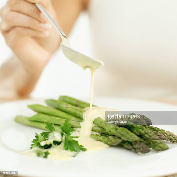 close-up of a woman's hand dressing stalks of asparagus with cream