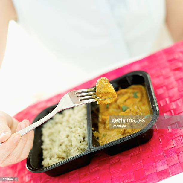 Close-up of a woman's hand eating chicken curry with a fork