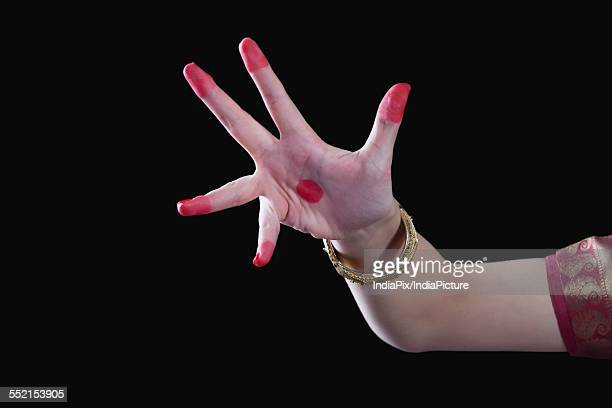 Close-up of a womans hand making Bharatanatyam gesture called Alapadma on black background