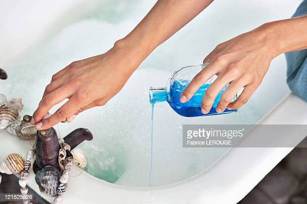 Close-up of a woman's hand pouring aromatherapy oil in a bathtub