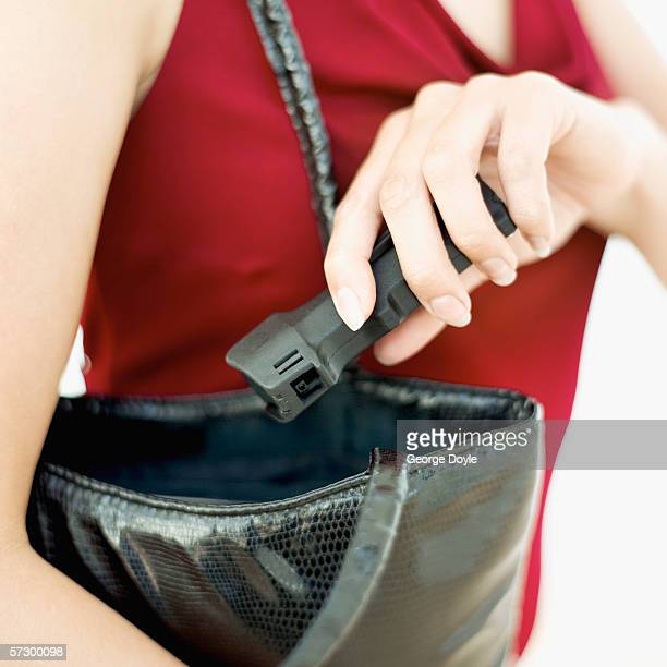 Close-up of a woman's hand removing a protective device from a handbag