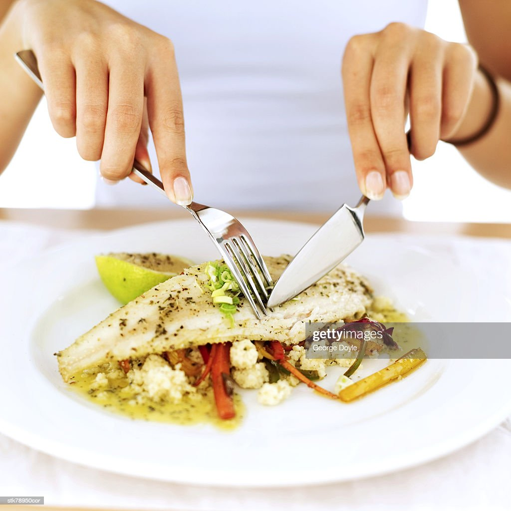 close-up of a woman's hands cutting a portion of food : Stock Photo