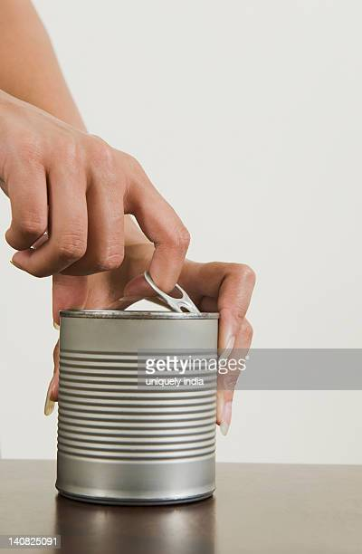 Close-up of a woman's hands opening a canned food