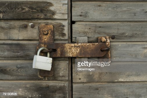 Close-up of a wooden door with a padlock : Stock Photo
