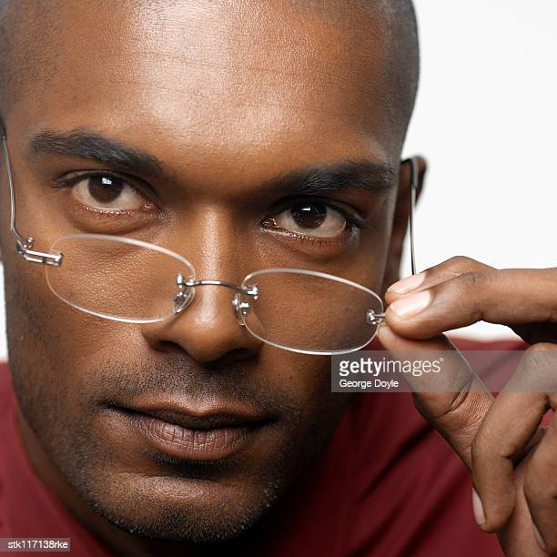 Close-up of a young businessman adjusting his glasses looking at camera