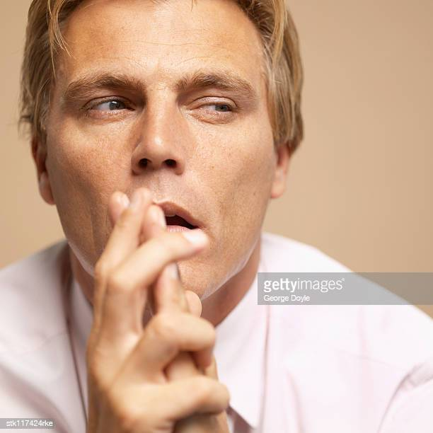 Close-up of a young businessman with his hands in front of his mouth