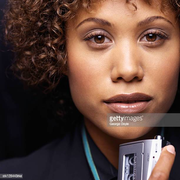 Close-up of a young businesswoman holding a Dictaphone