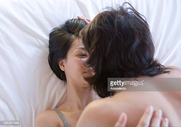 Close-up of a young couple romancing on the bed