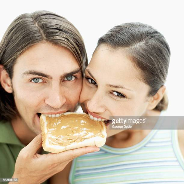 close-up of a young couple sharing a slice of bread with peanut butter