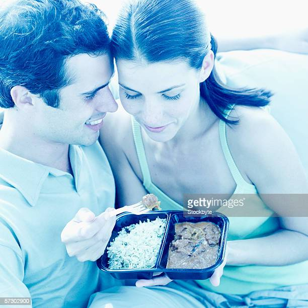 Close-up of a young couple sharing a tray of curry and rice