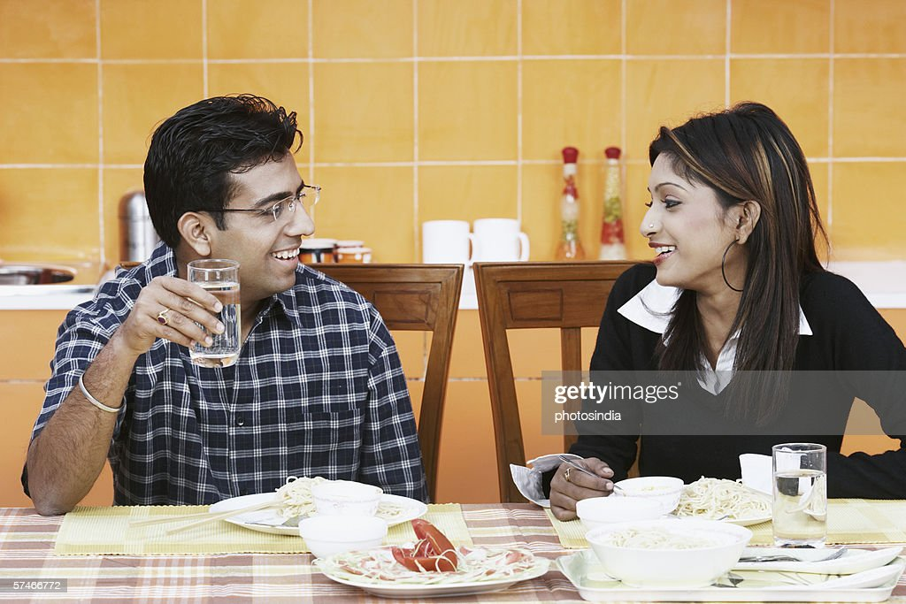 Close-up of a young couple sitting at the dining table : Stock Photo