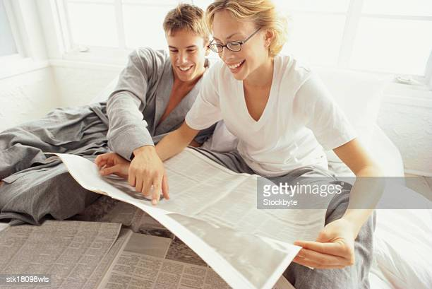 close-up of a young couple sitting together and reading the newspapers
