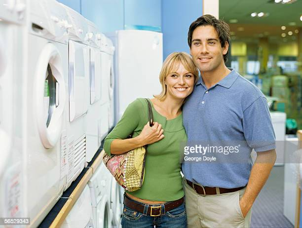 close-up of a young couple standing in an electronics store